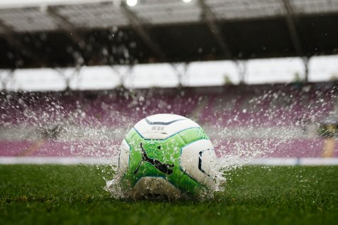 A soccer ball thrown by referee Klossner lands on the pitch after he decided to postpone the Swiss Super League soccer match between Servette FC and FC Sion due to heavy rain in Geneva
